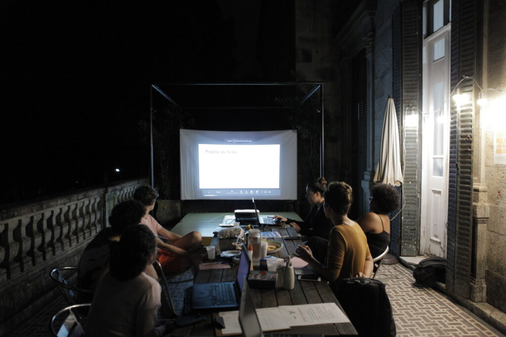 A group of people, around a table in dark room looking at a screen together. Image from the Art+Feminism Wikipedia Edit-a-thon in Rio, Brazil on March 10 at the balcony of EAV's library. Photo by Gabi Carrera.