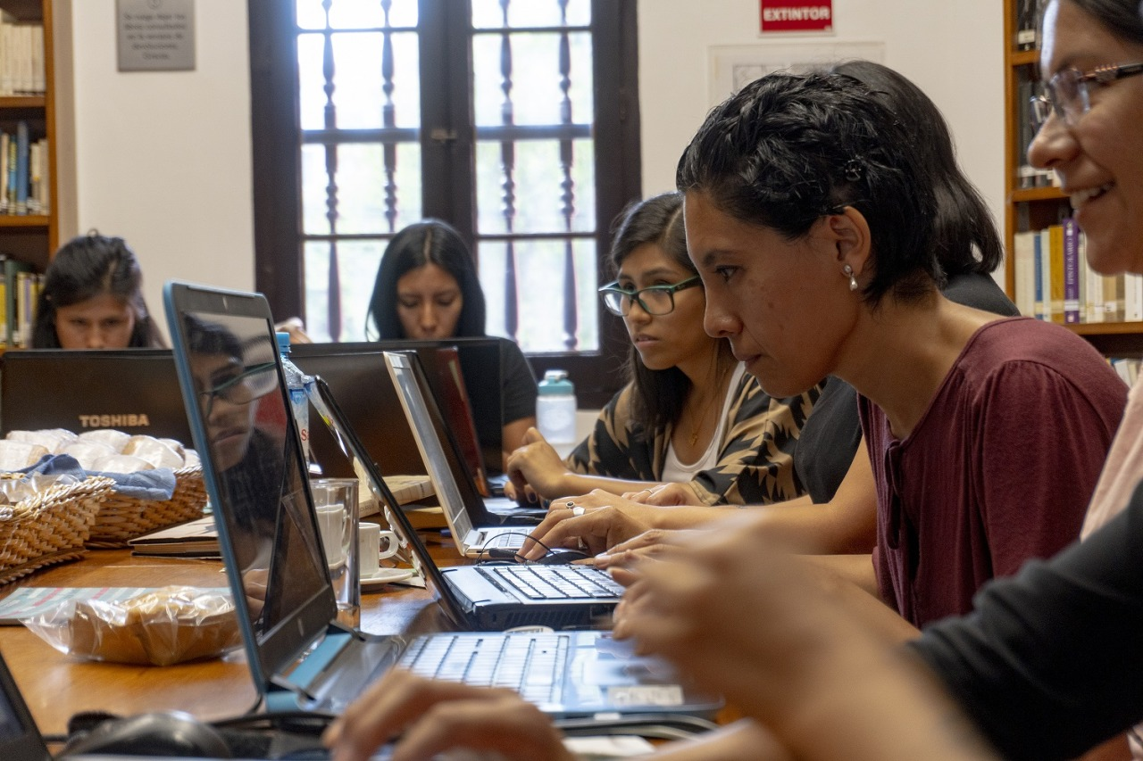 close-up photo with people gathered around a table with laptops, working at them. Image from sixth Art + Feminism Edit-a-thon in Lima was held on March 7 at the Cultural Center of Spain in Lima. Photo courtesy of Centro Cultural de España en Lima.]