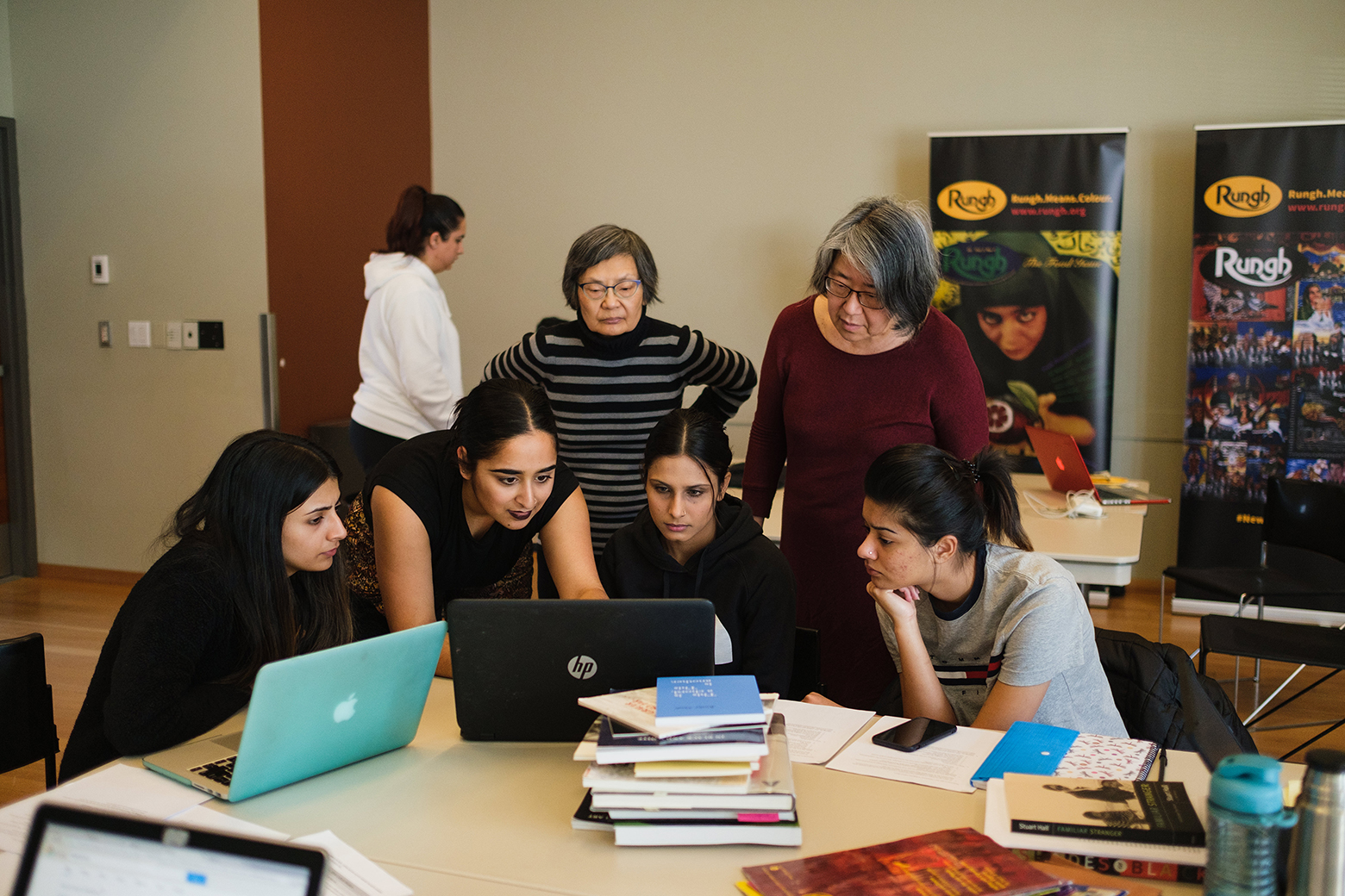 A group of people of all ages gathered around a computer on a table with books and laptops. Image from Wikipedia Edit-a-thon form 2019. Photo by Pardeep Singh.