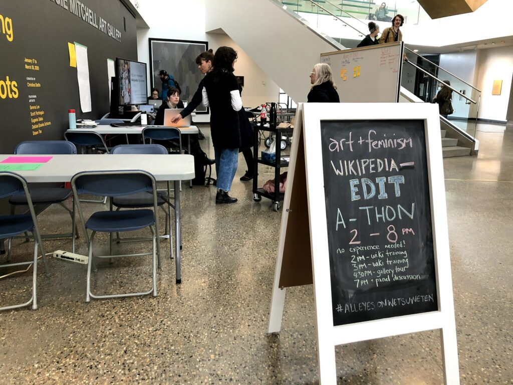 A chalk sandwich board advertising the schedule for the YEG A+F edit-a-thon at Allard Hall.
